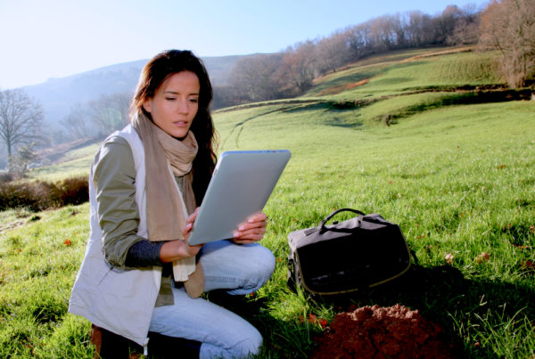 Woman out in a field looking at data from her business intelligence solutions on a tablet