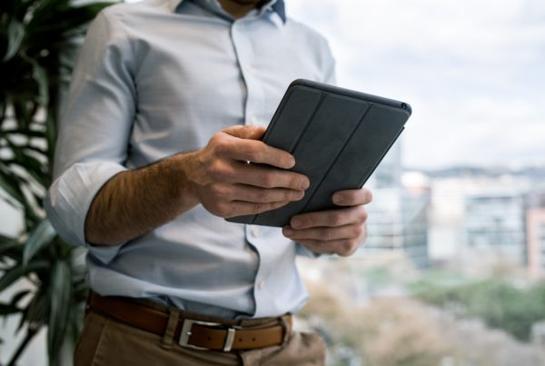 What is ad hoc reporting? Header image of man using tablet.